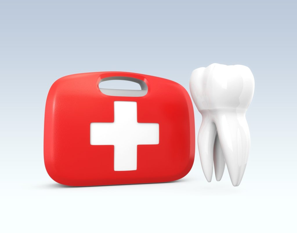 red first-aid kit with a white cross next to a white tooth representing emergency dentistry services at Summit Family Dentistry in Denver, North Carolina