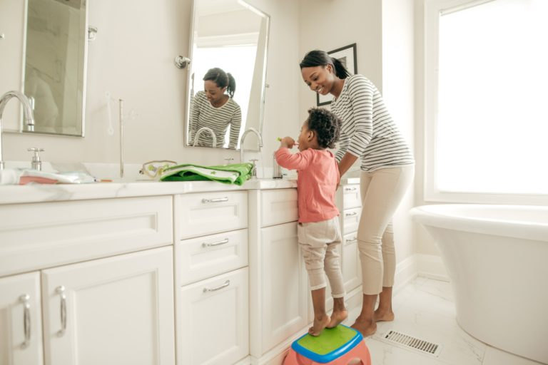 Image of mom and kid brushing teeth at the bathroom sink looking in the mirror, Summit Family Dentistry, Denver, North Carolina