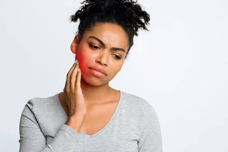 African American woman holding her jaw due to tooth ache and needs root canal