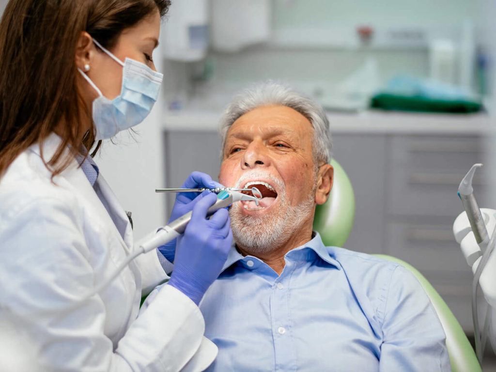 a senior-aged man, receiving care at the dentist