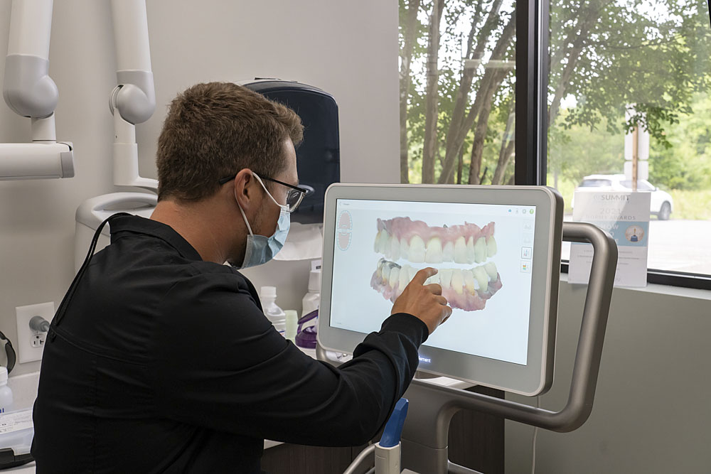 dentist pointing at a screen displaying a 3d model of teeth